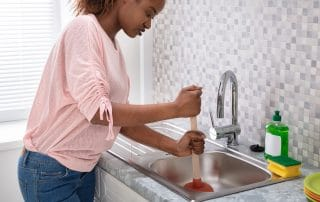Side View Of A Female Plumber Using Plunger In Kitchen Sink