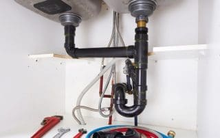 Plumbing repair tools underneath a kitchen sink